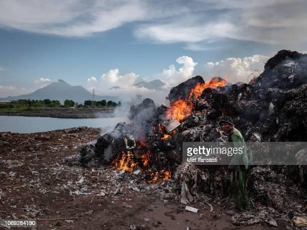 Man burns plastic waste at a import plastic waste dump in Mojokerto on December 4, 2018 in Mojokerto, East Java, Indonesia. Indonesia's...