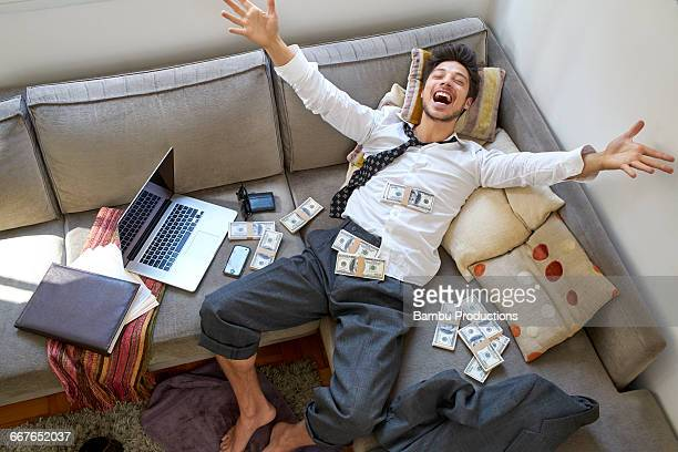 man bursting with joy with lots of money