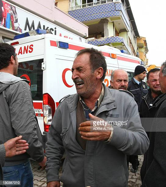 A man bursts into tears as rescue workers retrieved the dead body of his relative in Ercis province of Van eastern Turkey on October 26 2011 Prime...