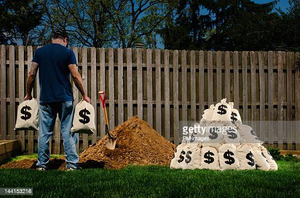 man burying $ bags in back yard - enterrar imagens e fotografias de stock