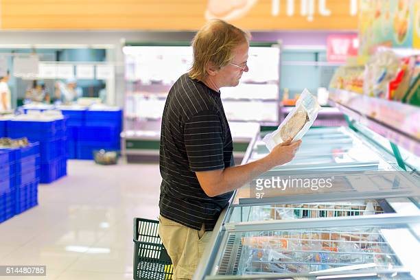 man buy frozen fish in the supermarket