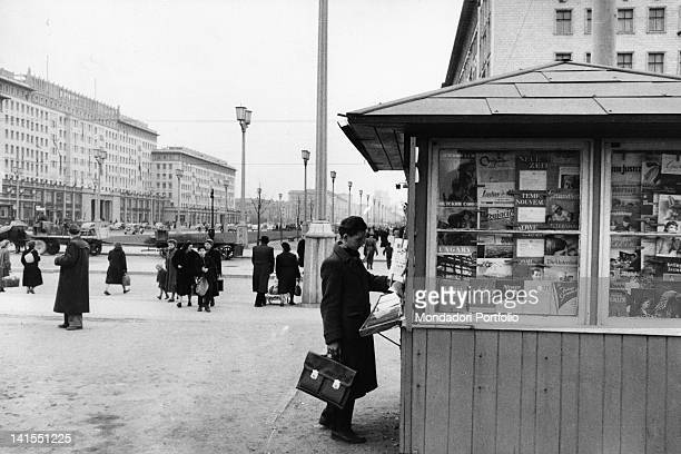 A man buying a magazine at a news stand in East Berlin Berlin March 1956