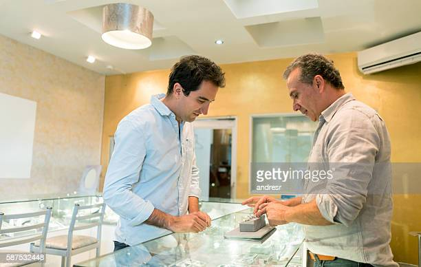 man buying an engagement ring - jeweller stock photos and pictures