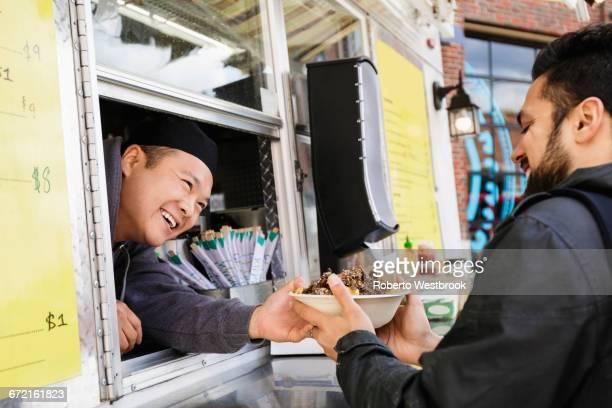 Man buying bowl of food at food truck