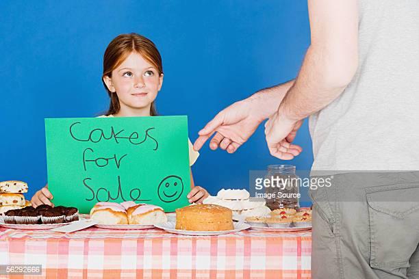 Man buying cake from girl
