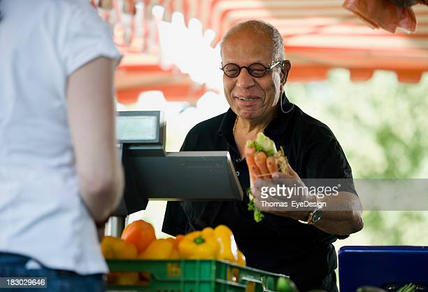 Man Buying Carrots at an Outdoor Market