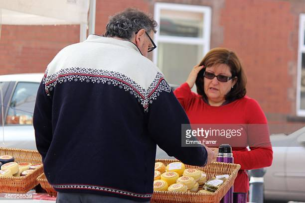 Man buying cheese at a weekend farmer's market held in Prestwich North Manchester England