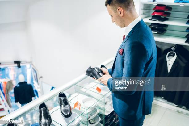 man buying choosing shoes - menswear stock pictures, royalty-free photos & images
