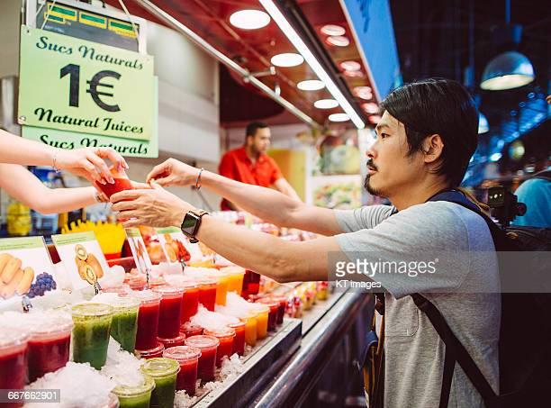 Man buying fresh juice at market