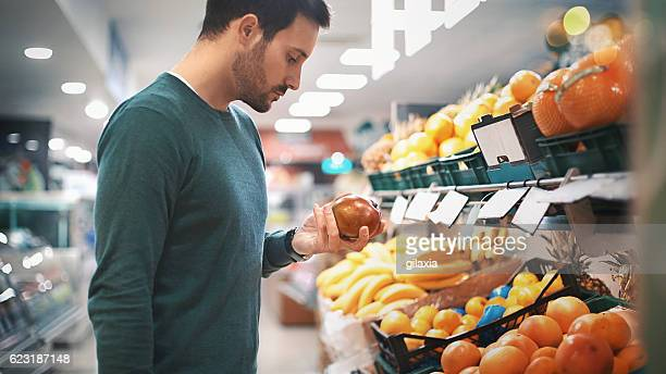 man buying fruit in supermarket. - convenient store stock photos and pictures