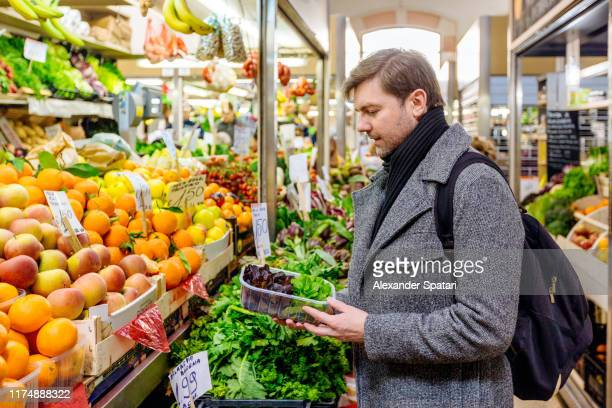 man buying groceries at the farmer's market - vegetarianism stock pictures, royalty-free photos & images