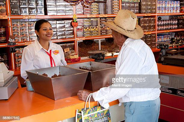 Man buying ground chocolate from woman in a shop, Oaxaca, Mexico