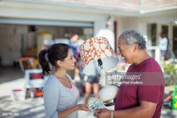 Man buying lamp at yard sale