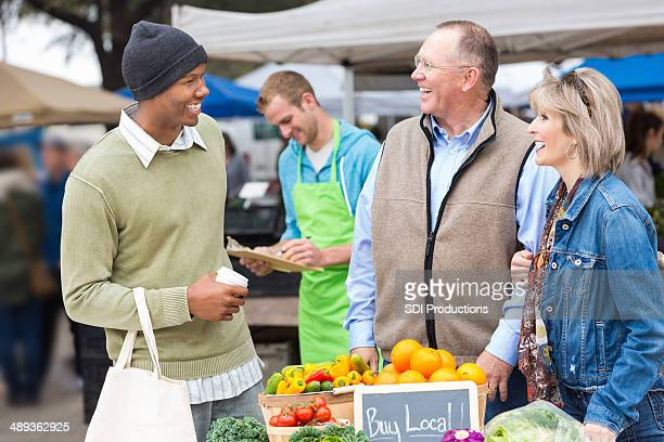 Man buying local produce from senior couple at farmer's market