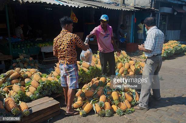 Man buying pineapples at Manning Market