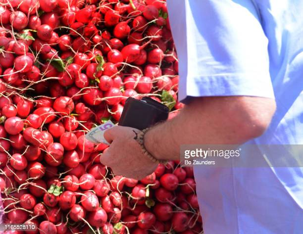 man buying radishes at the union square green market in new york city. - image stock pictures, royalty-free photos & images