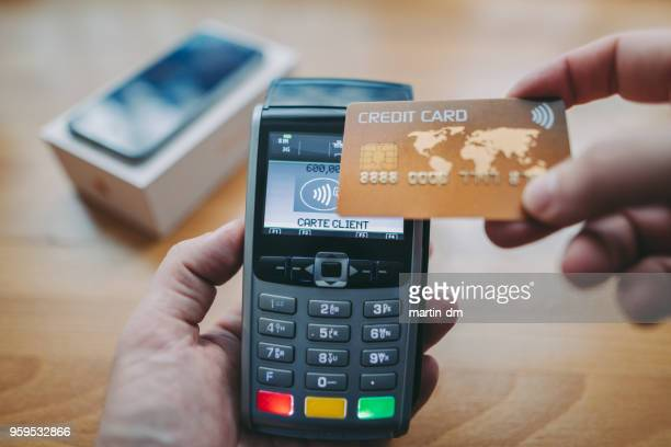 man buying smartphone with contactless credit card - credit card reader stock pictures, royalty-free photos & images