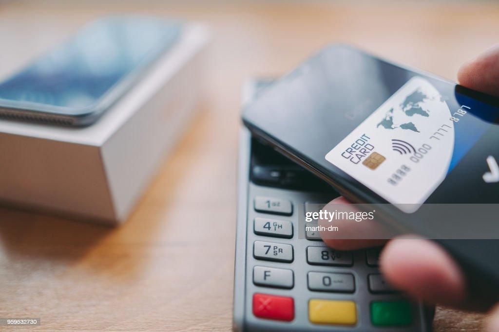 Mann kauft Smartphone mit digital wallet : Stock-Foto