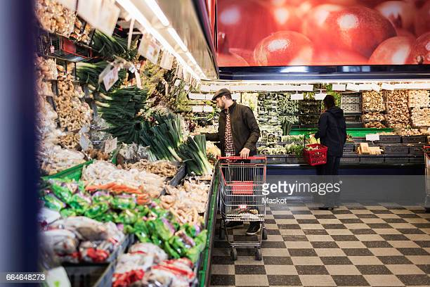 Man buying vegetables while holding shopping cart in supermarket