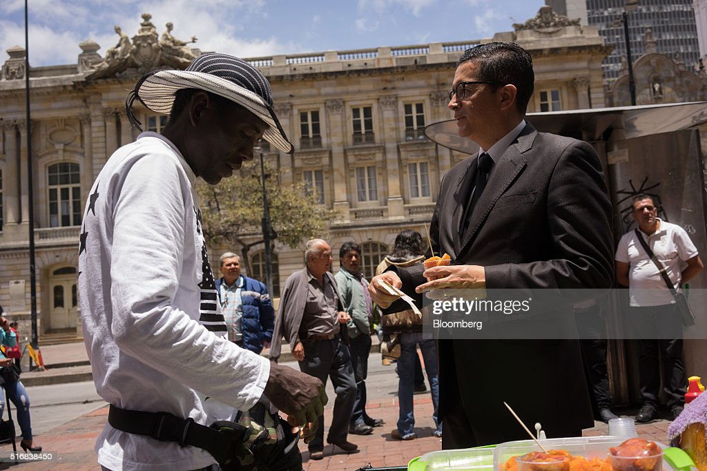 A man buys a cup of borojo fruit from a street vendor in Bogota, Colombia, on Wednesday, March 16, 2016. Colombia's central bank raised its benchmark interest rate for a seventh straight month as the inflation outlook continued to worsen and economic growth unexpectedly accelerated. Photographer: Mariana Greif Etchebehere/Bloomberg via Getty Images