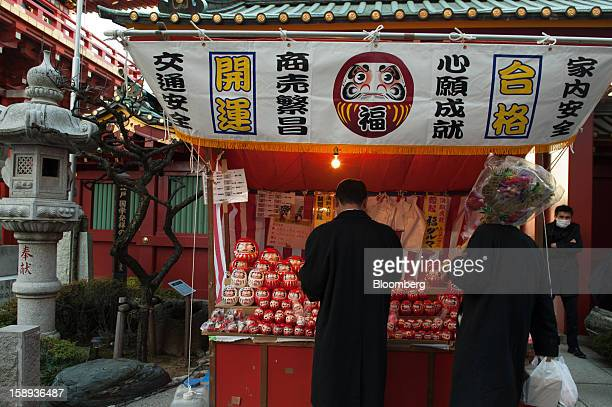 A man buys a Daruma doll for good luck on the first day of business in 2013 at the Kanda Myojin shrine in Tokyo Japan on Friday Jan 4 2013 Japan's...