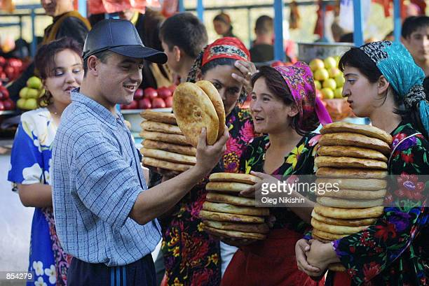 A man buys bread at a market November 18 2001 in Termez Yzberistan near the YzberistanAfghanian border