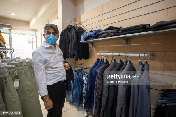 A man buys clothes in a downtown shop on May 23 2020 in Matera Italy Restaurants bars cafes hairdressers and other shops have reopened subject to...