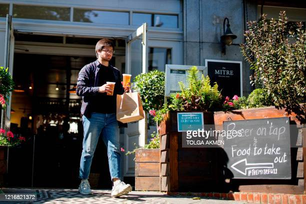 Man buys drinks from a pub open for takeaways on Holland Park Avenue in west London on June 1 following the easing of the lockdown restrictions...