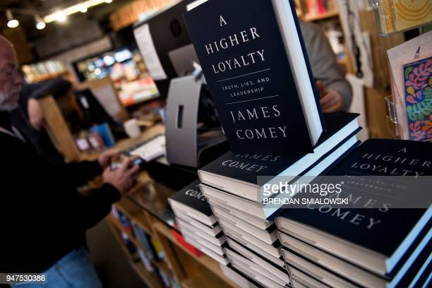 A man buys former FBI Director James Comey's new book A Higher Loyalty at Kramerbooks on April 17 in Washington DC / AFP PHOTO / Brendan Smialowski