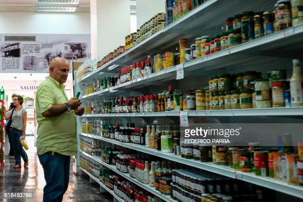 A man buys goods at a supermarket in Caracas on October 20 2016 Hit by the fall of global oil prices the economy in Venezuela has crashed and food...