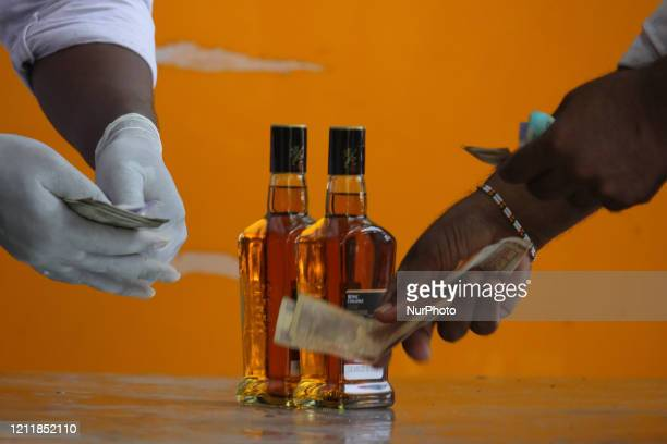 Man buys liquor at a wine store, after it was allowed to open in all except containment zones in Mumbai, India on May 05, 2020. India continues in...