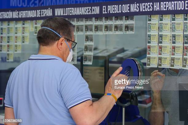 Man buys lottery in an Administration in Manises during the fourth day since the reopening of her business within the de-escalation process...
