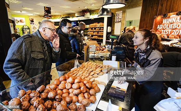 A man buys 'oliebollen' by donutmaker Richard Visser on December 31 2015 in Spijkernisse An oliebol is a donutlike product traditionally made and...