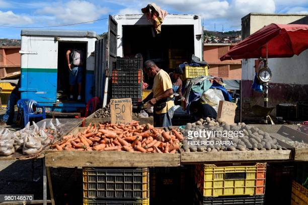 A man buys vegetables at the municipal market of Coche a neighbourhood of Caracas on June 20 2018 Venezuelan President Nicolas Maduro ordered the...