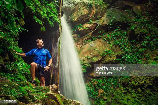 man by a small waterfall in costa rica