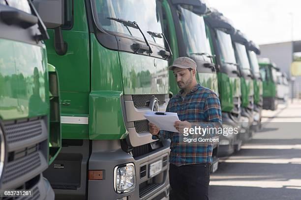 man by fleet of trucks looking at paperwork - sigrid gombert 個照片及圖片檔