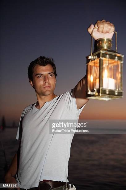 Man by ocean holding lantern up