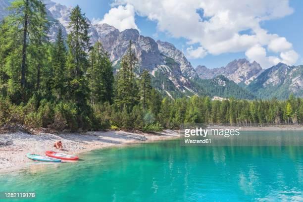 man by paddleboards at pragser wildsee lakeshore on sunny day, dolomites, alto adige, italy - seeufer stock-fotos und bilder