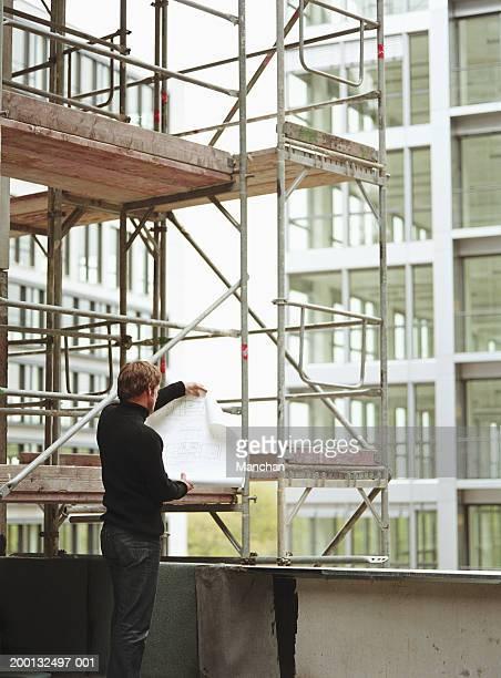 man by scaffolding on construction site, looking at blueprint - col roulé photos et images de collection