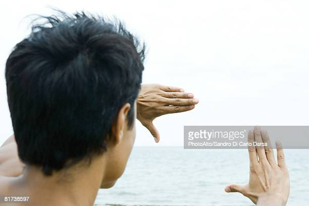Man by the sea, looking at view through finger frame