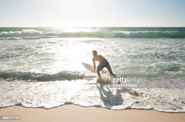Man by the sea with surfboard, surfing