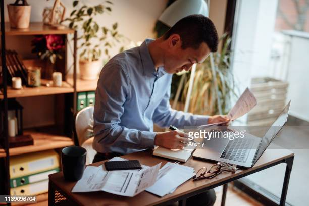 man calculating his financial bills - bank statement stock pictures, royalty-free photos & images