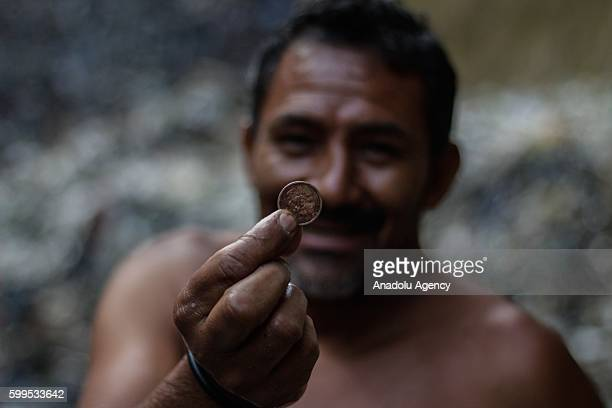A man called himself 'Miner' holds a valuable object after he found it inside tons of garbage on a river of toxic water that flows through the city...