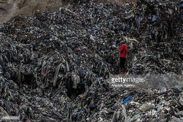 A man called himself 'Miner' observes tons of garbage on a river of toxic water that flows through the city dump in Guatemala on September 5 2016...