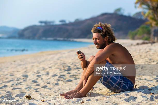 Man calling by phone on the beach.