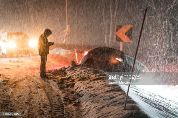 man calling for help for car accident in snow - extreem weer stockfoto's en -beelden