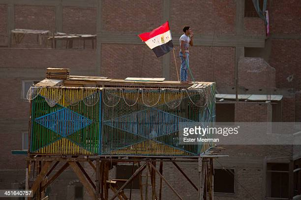 CONTENT] A man calls out to his pigeons while standing on a home made pigeon coop in the Garbage City district of Cairo Egypt