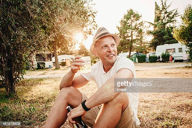 Man camping and drinking a beer outdoors