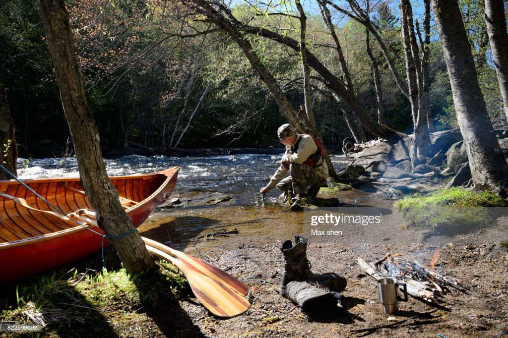 Man camping at the riverbank with a canoe : Stock Photo