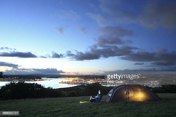 man camping in field with city and river view - キャンプ 1人 ストックフォトと画像